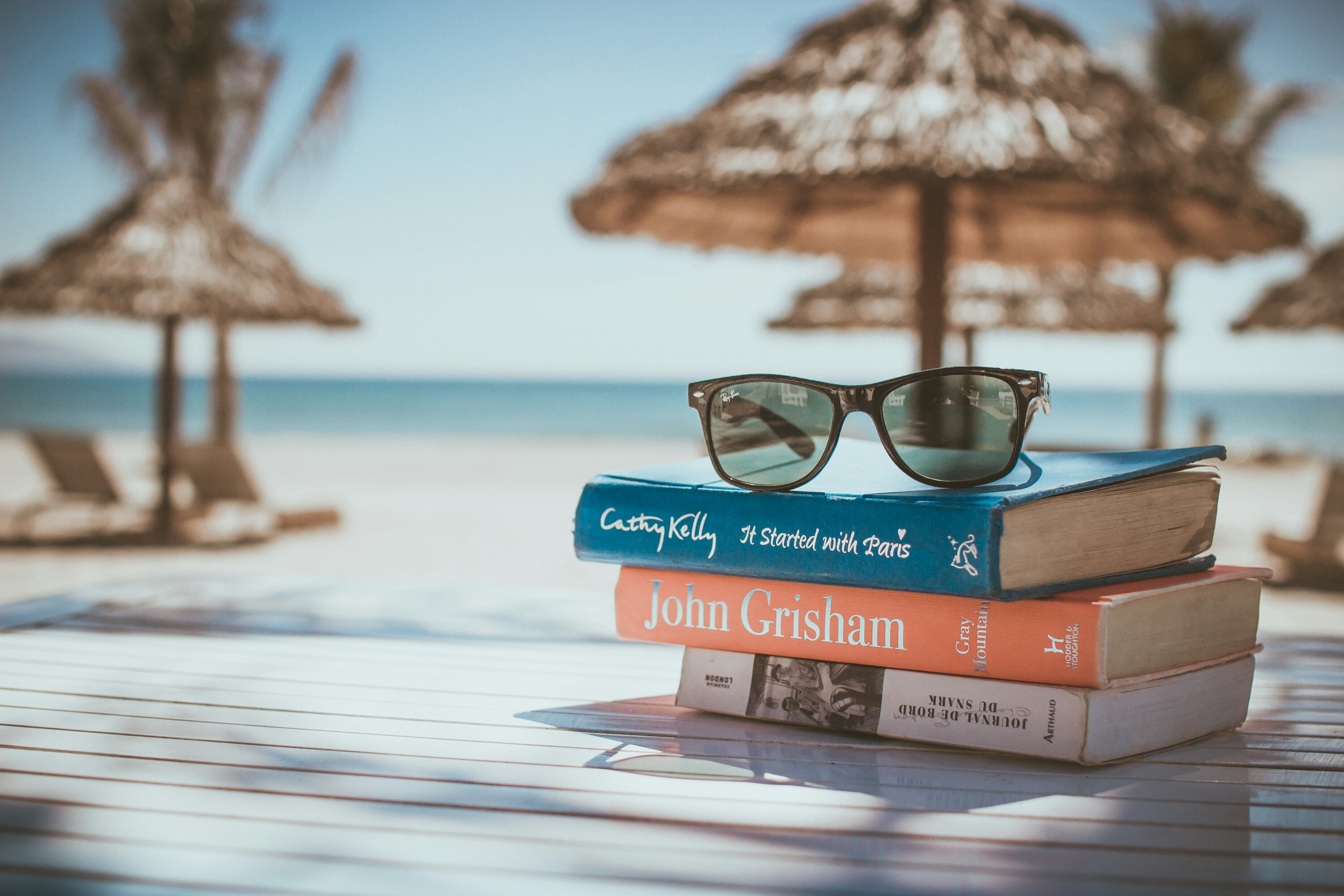 Vacation picture consisting books, sunnies and beach.