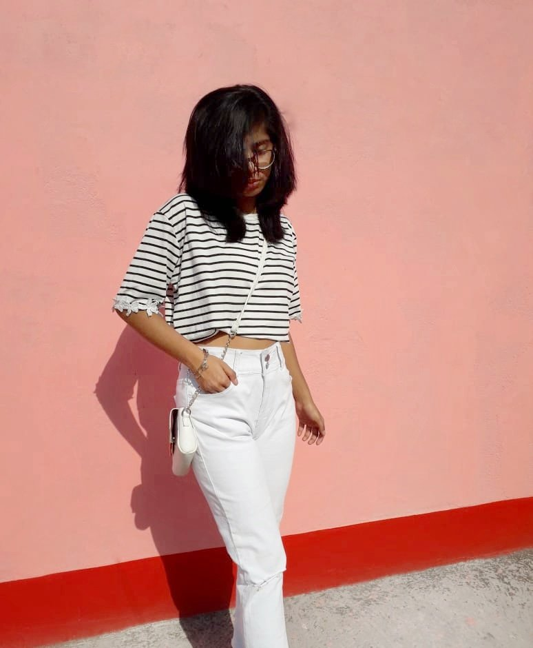 A striped crop tee paired with white high waist jeans.