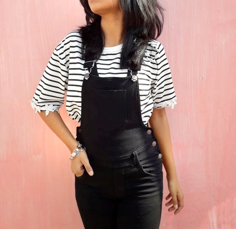 A striped crop tee paired with black overalls.