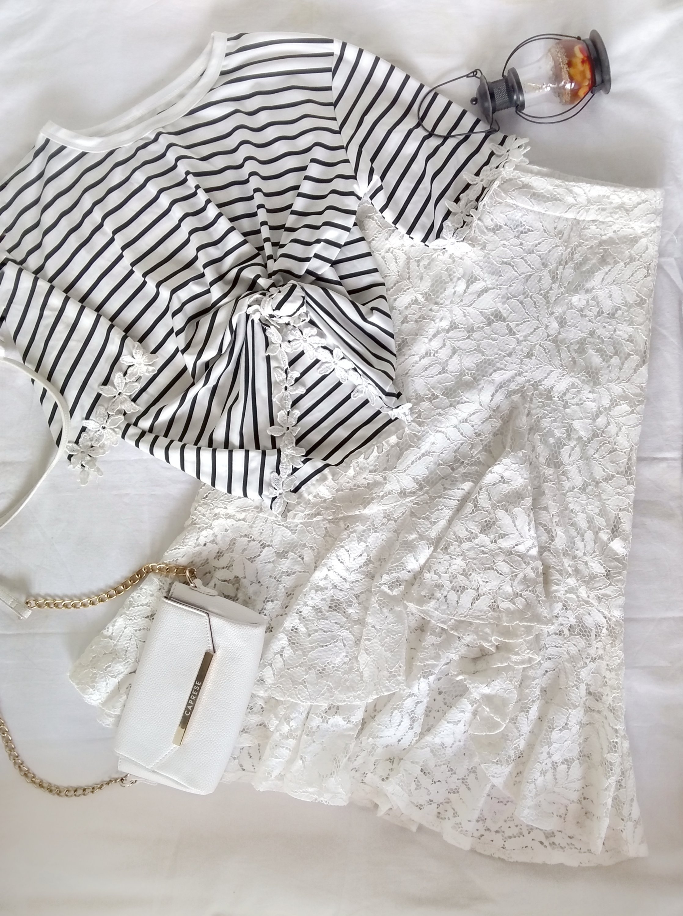 A lace-detailed tee paired with lace white midi skirt.