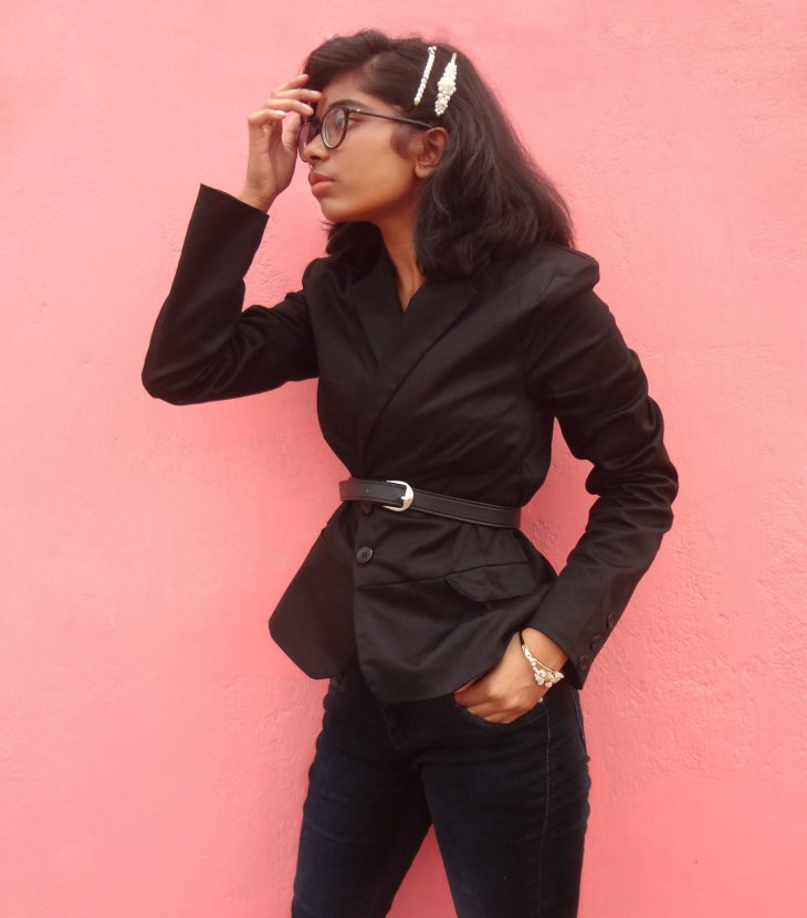 A chic all-black outfit styled with a belted blazer.