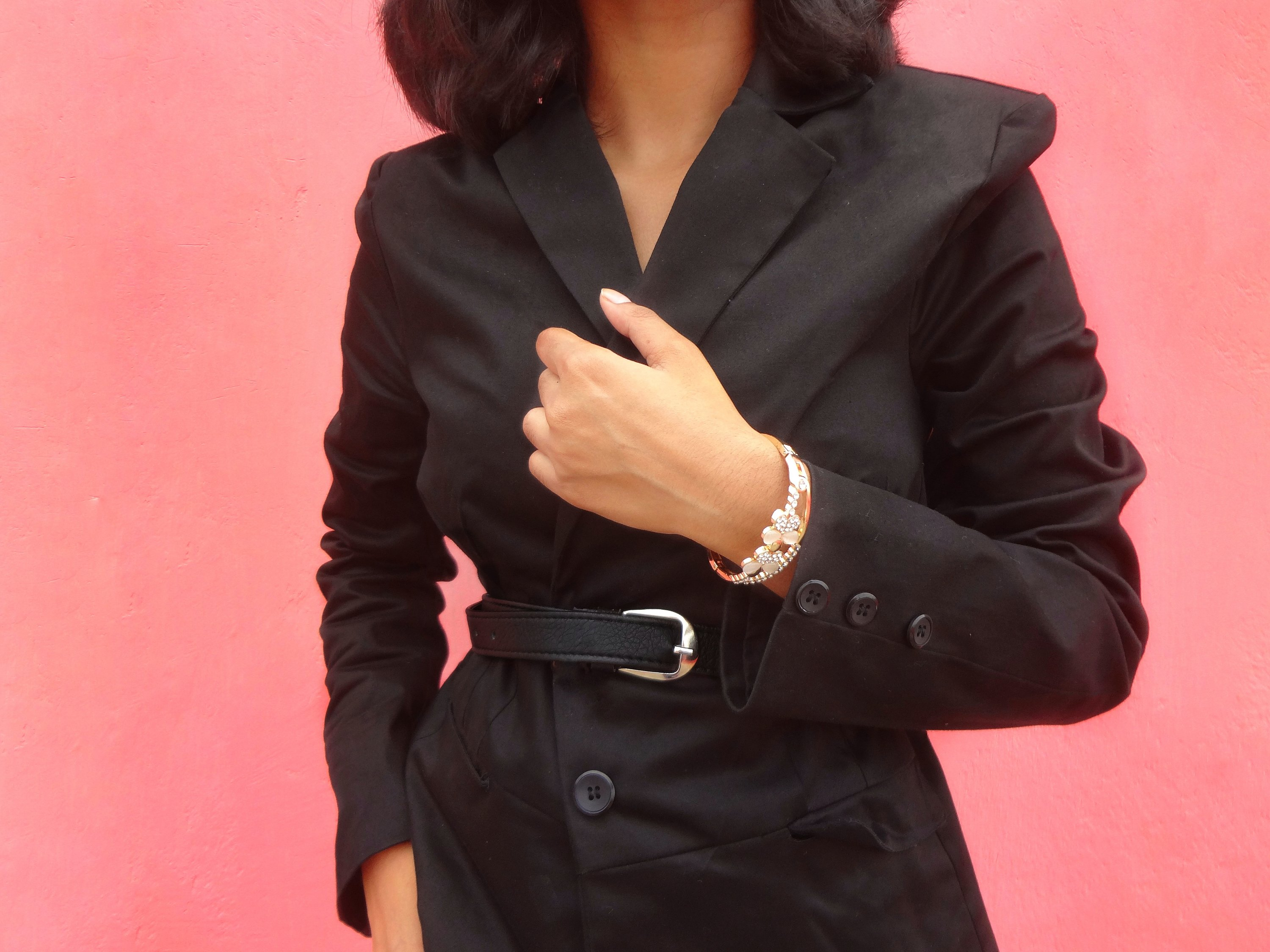 Belted blazer accessorized with a gold bracelet; outfit details