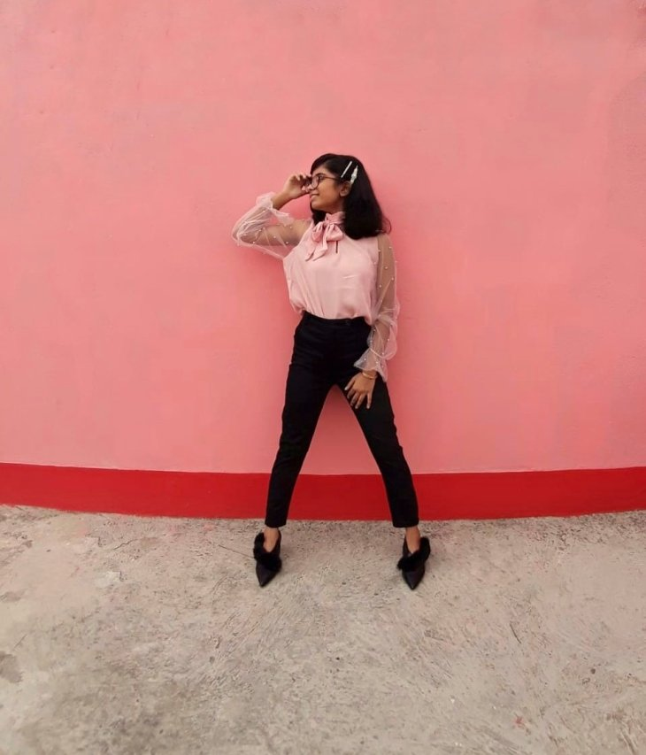 Chic business outfit consisting of millennial pink blouse paired with black pants and black kitten heels.