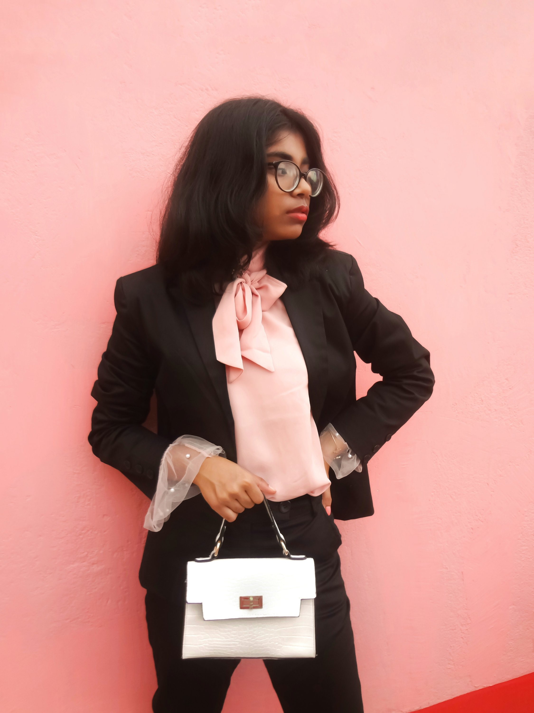 A black blazer topped with pink tulle blouse.