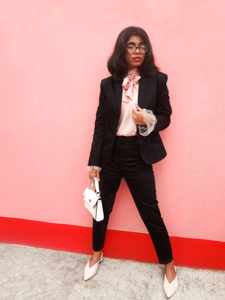 A black suit paired with pink tulle blouse white mules.